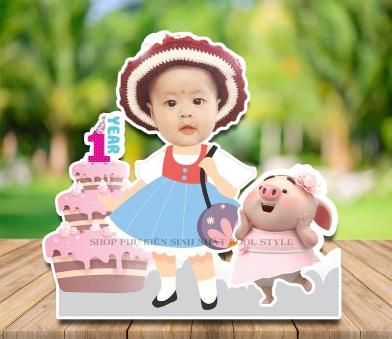 Chibi bé gái đứng cạnh bánh kem và heo con