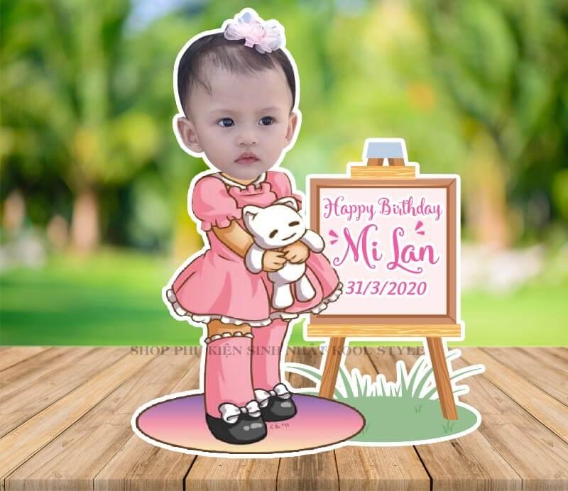 Chibi bé gái ôm búp bê đứng cạnh bảng sinh nhật