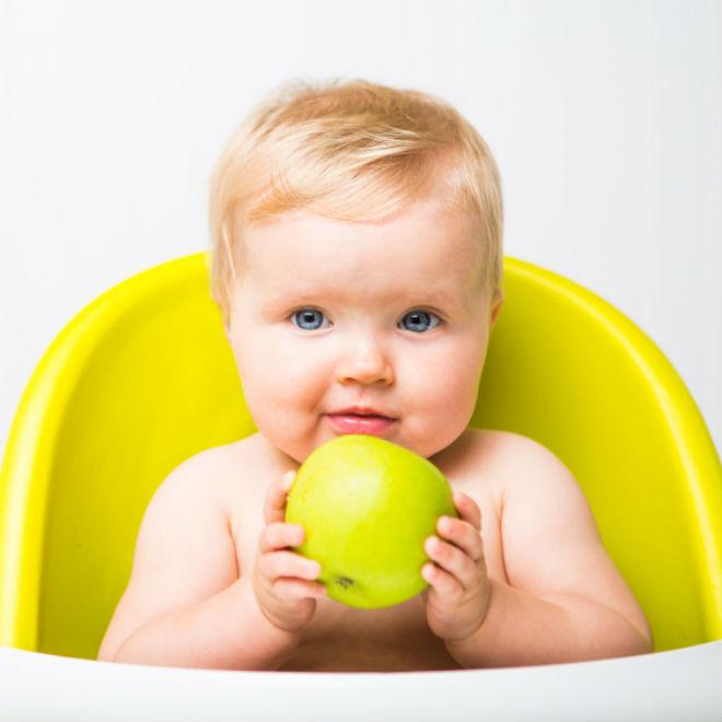 em bé cầm quả táo