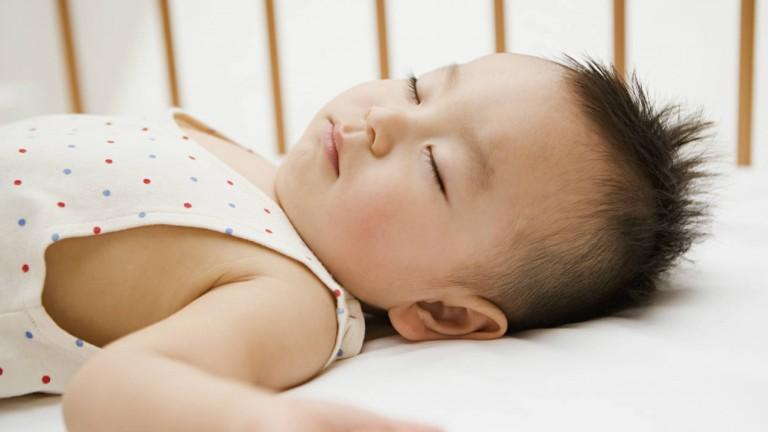 Một em bé ngủ trong cũi