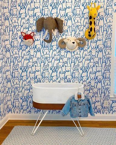 Một chiếc nôi giường cũi kỳ diệu phía trước hình nền nhà trẻ có in hình những chú chó bằng tay màu xanh lam.  Phía trên giường cũi kỳ diệu có một con hươu cao cổ, voi, cừu đực và cáo bằng nỉ sang trọng trên tường.