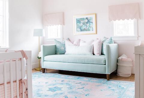 Phòng trẻ màu hồng nhạt với chiếc ghế dài màu xanh nhạt và tấm thảm có hoa văn màu xanh nhạt.