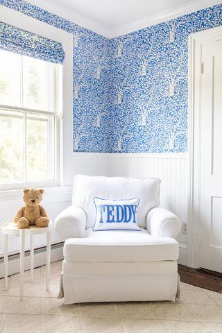 Một nhà trẻ màu xanh da trời với hình nền in hình chiếc lá màu xanh lam và các ô cửa sổ in hình chiếc lá phù hợp.