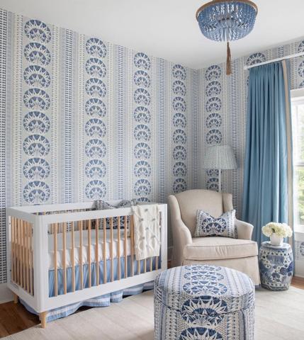 Một nhà trẻ với giấy dán tường in màu xanh trắng đậm — họa tiết tương tự xuất hiện trên gối và ghế dài trong phòng.