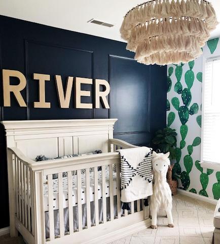 Một nhà trẻ với bức tường sơn màu xanh đậm và chữ RIVER được in bằng vàng phía sau cũi.  Bức tường bên cạnh có giấy dán tường in hình cây xương rồng màu xanh lá cây.