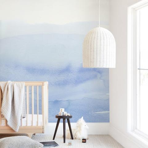 Một nhà trẻ màu xanh da trời với bức tranh tường màu nước xanh nhạt trên bức tường phía sau cũi.