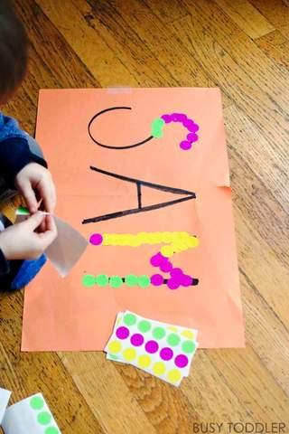 Trẻ mới biết đi sử dụng dấu chấm để theo dõi tên SAM trên một mảnh giấy.