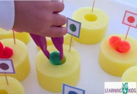 Một đứa trẻ mới biết đi sử dụng kẹp nhựa để đặt pom-pom vào các miếng hình bánh rán của một sợi mì hồ bơi đã cắt sẵn.