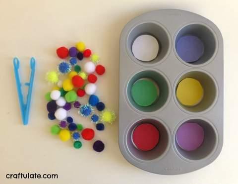 Kẹp kẹp bằng nhựa, quả pom-pom nhiều màu sắc và hộp thiếc bánh nướng xốp.