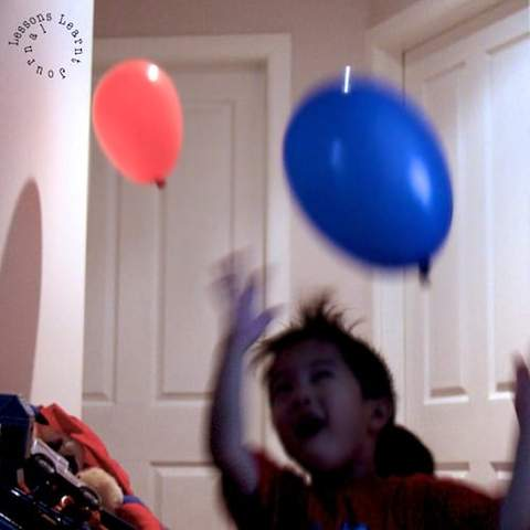 Một đứa trẻ mới biết đi dơi hai quả bóng bay xung quanh nhà của mình.