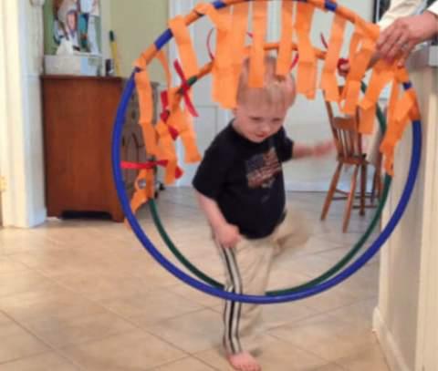 Trẻ mới biết đi leo qua vòng hoa hula được trang trí bằng dải màu cam.