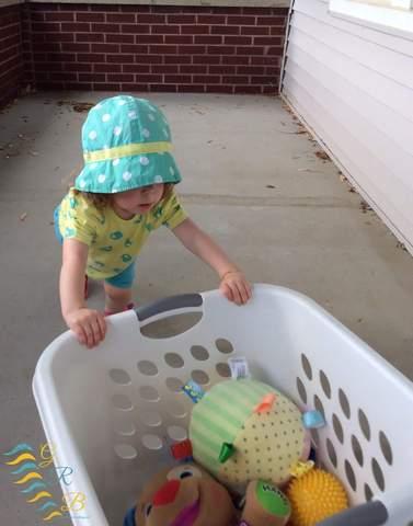 Trẻ mới biết đi đẩy giỏ giặt chứa đầy đồ chơi.