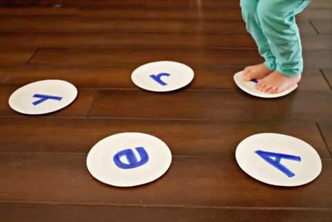 Trẻ mới biết đi nhảy lên đĩa giấy được trang trí bằng các chữ cái khác nhau.