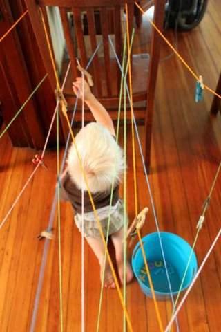 Trẻ mới biết đi cố gắng vượt qua mê cung được làm bằng dây.