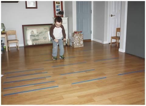 Trẻ mới biết đi trong phòng khách nhảy qua các đường băng trên sàn.