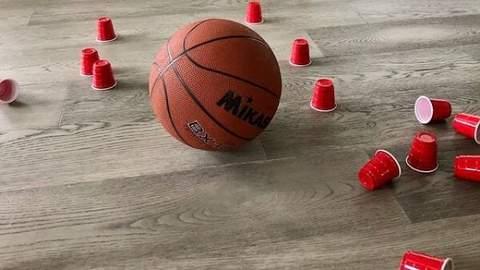 Một quả bóng rổ trên sàn gần những chiếc cốc nhựa bị đổ sau một trận bowling tự chế.