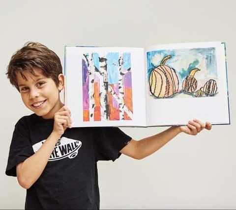 Đứa trẻ cầm cuốn sách đóng bìa các tác phẩm nghệ thuật của mình