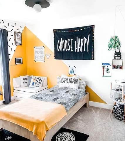 Phòng ngủ đồ họa màu đen, trắng và vàng cho trẻ mới biết đi.