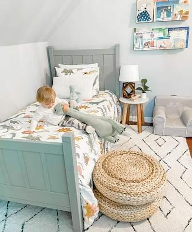 Phòng dành cho trẻ mới biết đi với tông màu bạc hà và bộ khăn trải giường hình khủng long.