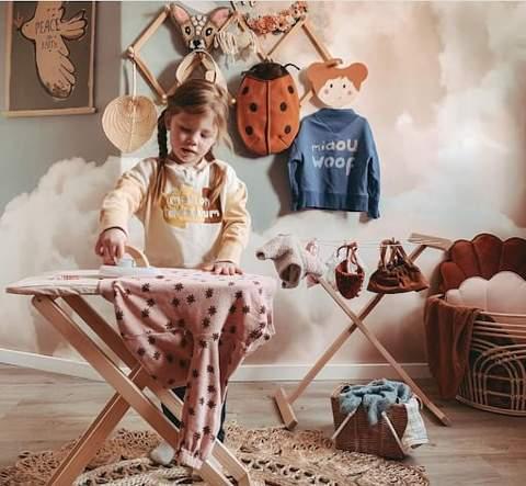 Trẻ mới biết đi đang giả vờ ủi trên bàn ủi giả trong không gian vui chơi của phòng trẻ mới biết đi.