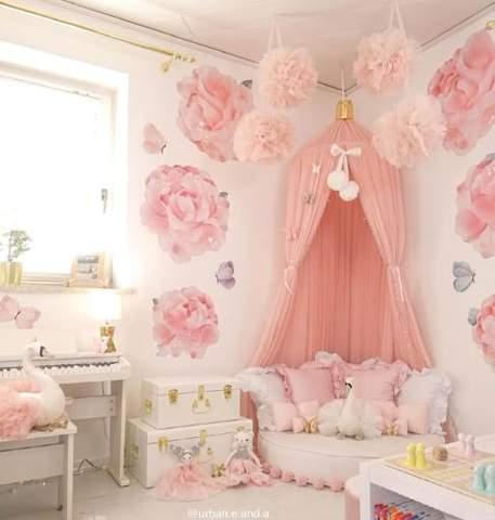Phòng ngủ cho trẻ mới biết đi màu hồng với tấm trải giường màu hồng và giấy dán tường hoa.