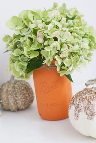 Những bông hoa xanh nhạt trong lọ thợ xây bằng đất nung và những quả bí ngô lấp lánh để tắm cho em bé vào mùa thu