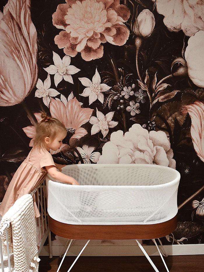 chị lớn đến thăm nhà trẻ của em gái với hình nền hoa và nôi SNOO