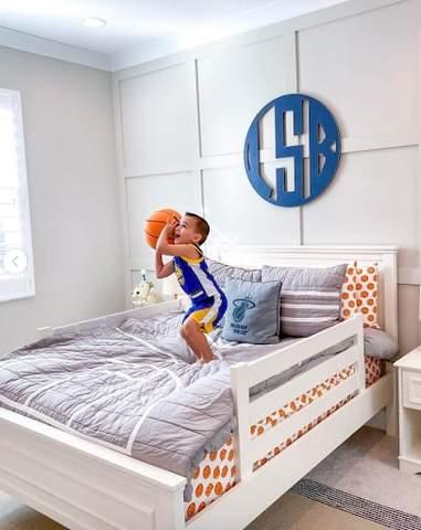 Trẻ mới biết đi đứng trên giường có tấm trải giường in hình bóng rổ, sẵn sàng bắn bóng rổ.
