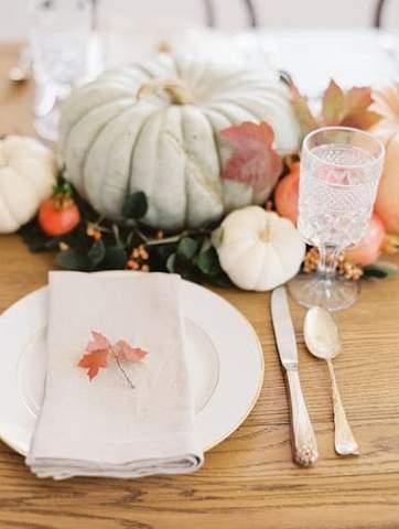 Bộ bàn ăn có bí ngô màu phấn, thêm và một chiếc lá nhỏ trên khăn ăn gấp màu trắng để tắm cho em bé vào mùa thu