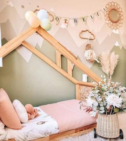 Giường tầng cho trẻ mới biết đi trong phòng trẻ mới biết đi màu hồng và xanh lá cây.