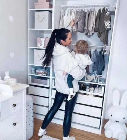 Mẹ và đứa trẻ mới biết đi nhìn quần áo treo trong tủ mở.