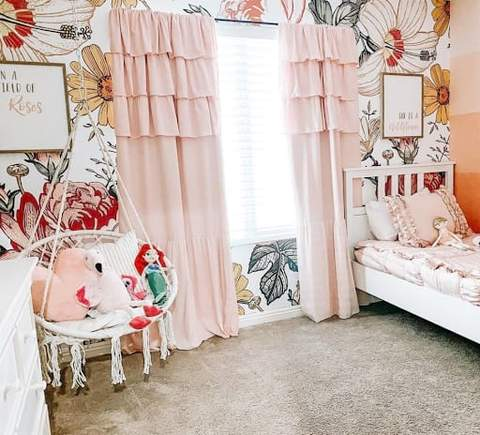 Phòng ngủ cho trẻ mới biết đi với giấy dán tường in hoa, rèm cửa màu hồng và một chiếc xích đu bằng liễu gai màu trắng treo trên trần nhà.