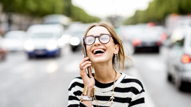 Người phụ nữ vừa cười vừa nói chuyện điện thoại trên phố