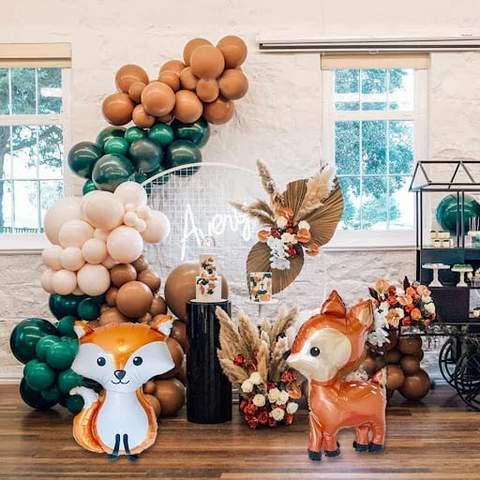 Bóng bay màu xanh ngọc lục bảo, kem, nâu và cáo và hươu được trưng bày trong buổi tắm mùa thu cho bé